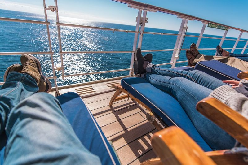 Low section of people relaxing on boat in sea during sunny day