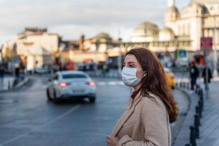Woman standing on city street in winter