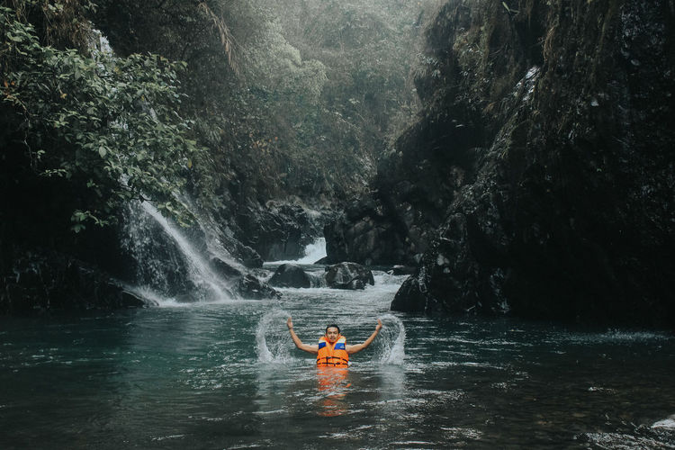 Man surfing in river against trees in forest