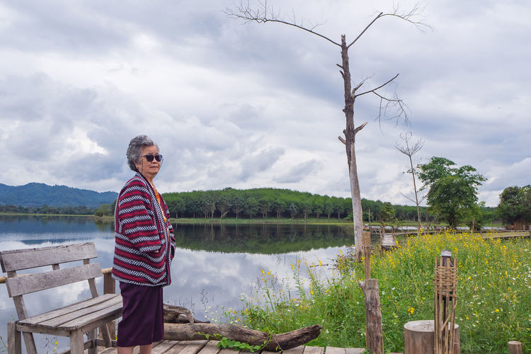 Portrait of elderly woman wearing sunglasses standing side the lake