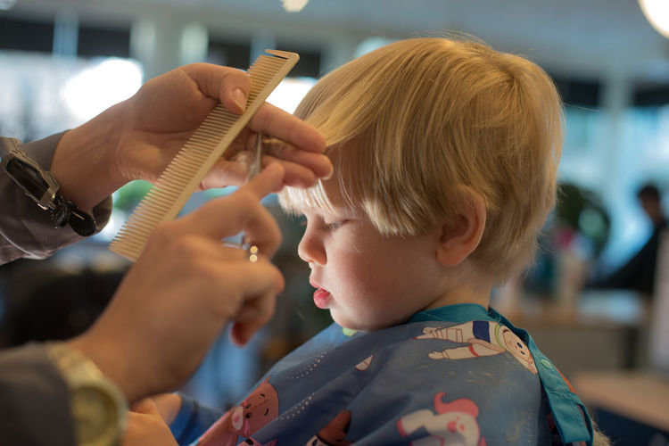 Cropped image of barber cutting boy hair