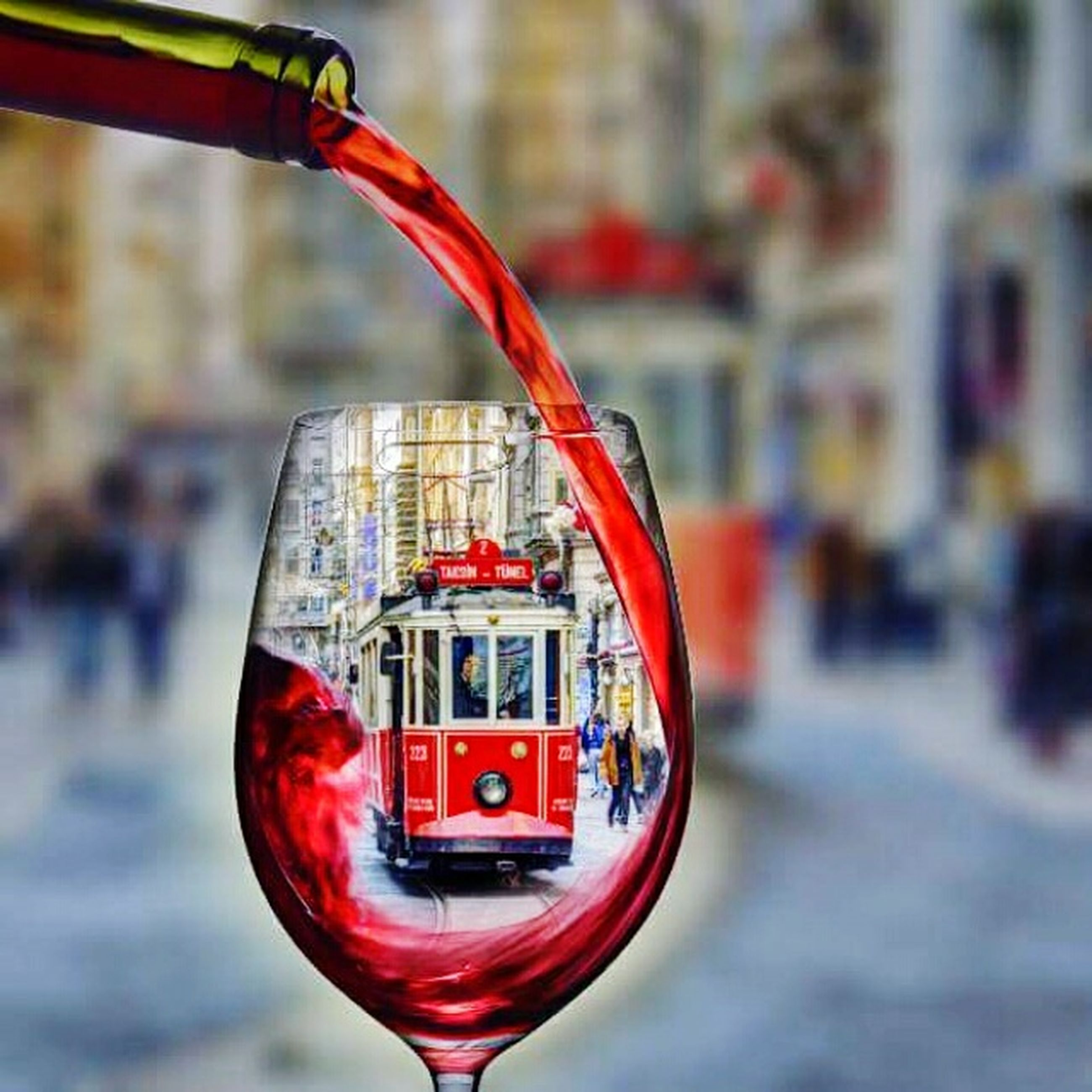 focus on foreground, red, building exterior, architecture, built structure, transparent, close-up, reflection, glass - material, city, incidental people, mid-air, outdoors, day, water, flying, window, street, no people, selective focus