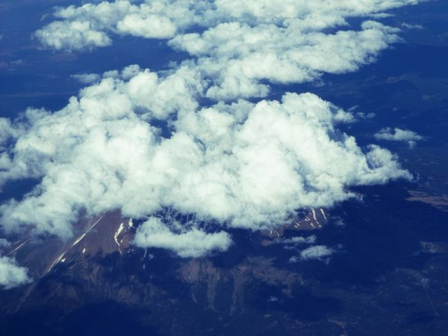 Mount Shasta surrounded in clouds from high up in an airplane. Aerial View Atmosphere Beauty In Nature Blue Cloud - Sky Cloudscape Day Dreamlike Environment Ethereal Fluffy Heaven Idyllic Majestic Mountain Nature Non-urban Scene Outdoors Scenics Sea Tourism Tranquil Scene Tranquility White White Color