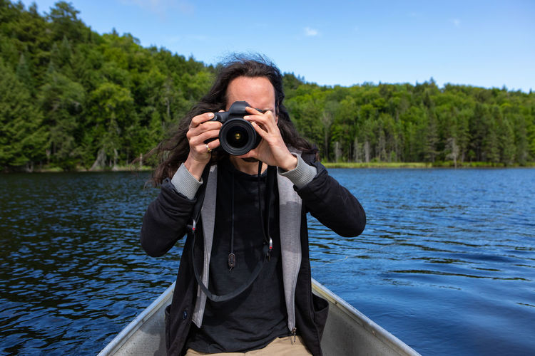 Portrait of man photographing against lake