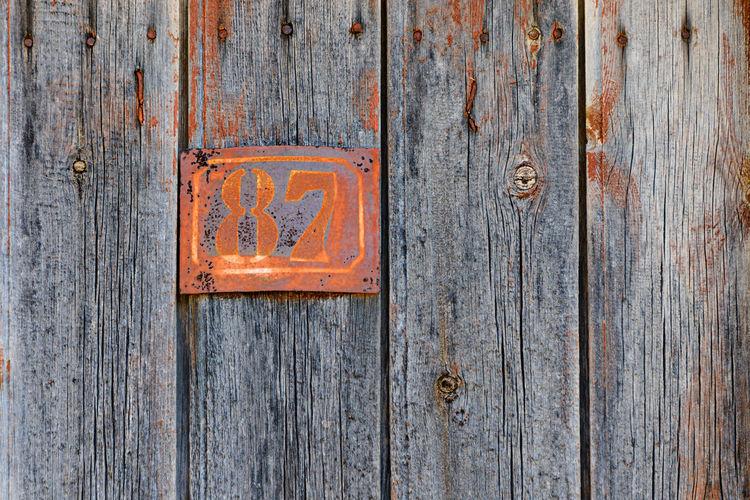 Rusty grunge metal house number plaque 87 on an old wooden door 87 Decay Rust Beauty In Decay Close-up Decayed Beauty Grunge Grungy House Number House Number Plaque House Number Plate House Numbers Metal Number Number Of The House Numbers Old Oxidation Patina Plate Number Rusting Rusty Metal Vintage Wooden Wooden Door