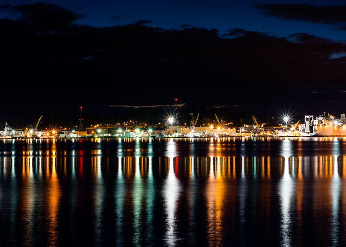 Lake by illuminated harbor against cloudy sky at night