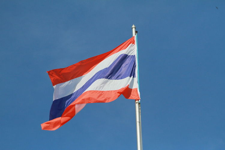 Low angle view of thai flag against blue sky
