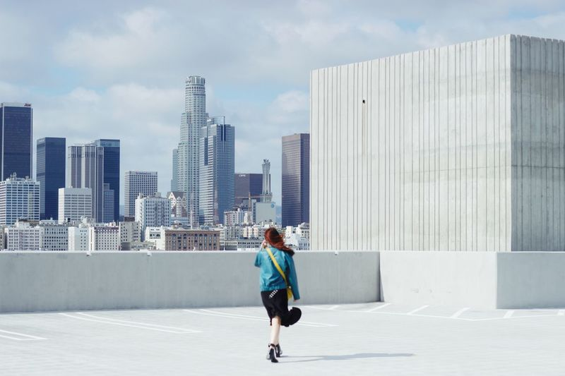 Rear View Of Woman Walking Against Modern Buildings
