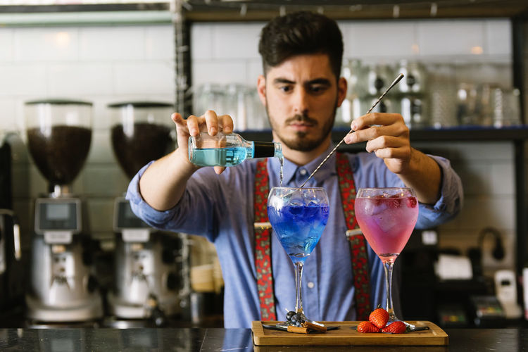 Midsection Of Bartender Making Drink