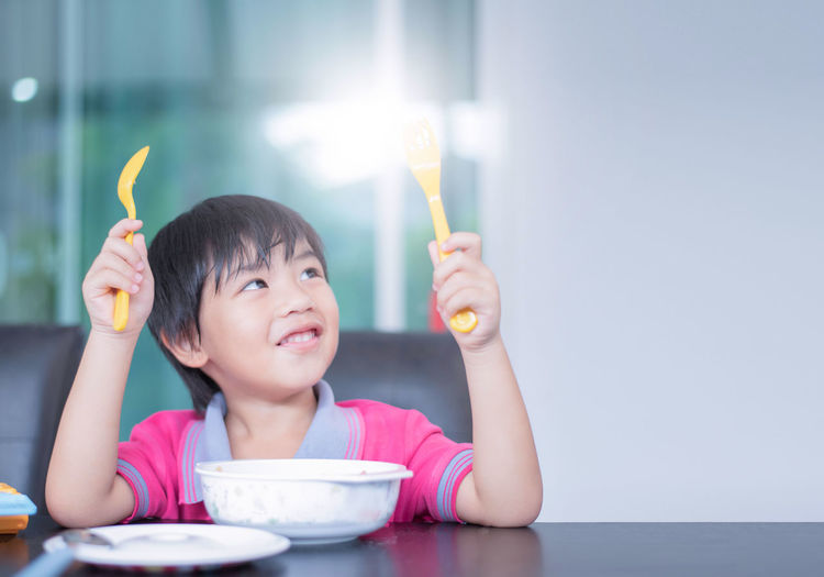 Portrait of cute boy eating food on table