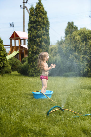 Side view of shirtless boy playing in yard