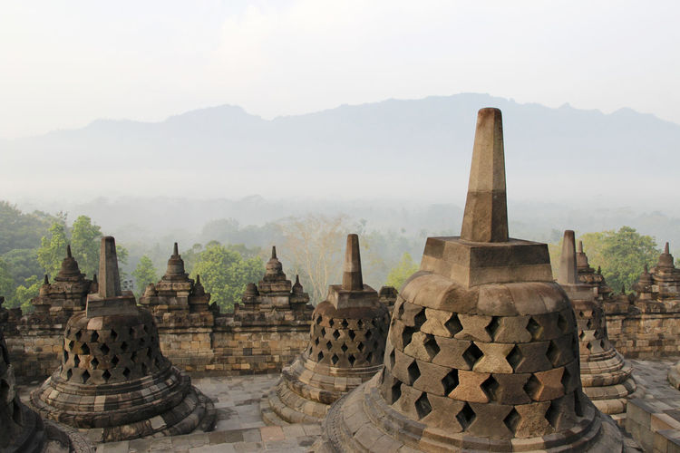 Borobudur Temple with the mysteries forest surrounding during sunrise, Yogyakarta, Indonesia Yogyakarta Ancient Ancient Civilization Architecture Architecture And Art Belief Borobudur Buddhist Temple Built Structure Carving Fog Forest History No People Outdoors Place Of Worship Religion Spirituality Stone Material Sunrise The Past Tourism Travel Travel Destinations