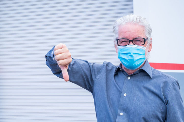 Portrait of man wearing mask gesturing thumb down while standing against shutter