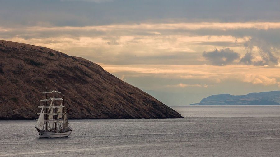 Ship Sailing In Sea By Mountains Against Sky During Sunset