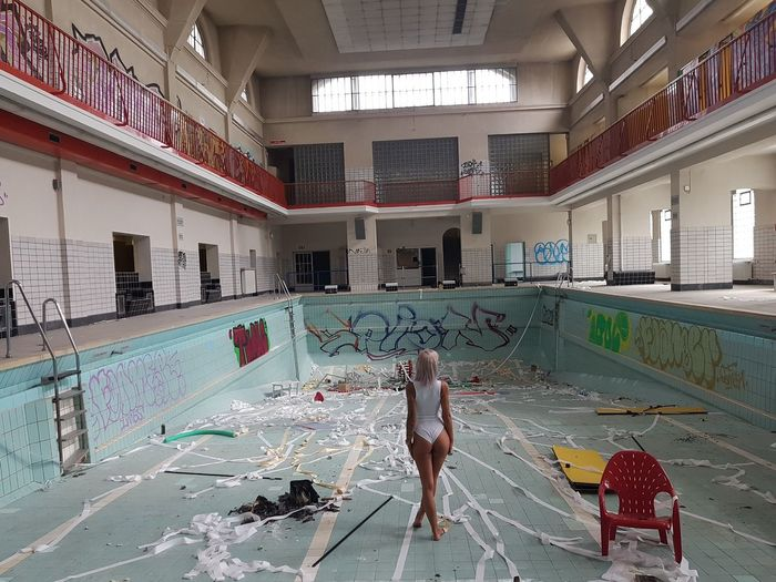 Rear View Of Woman Standing In Dried Swimming Pool