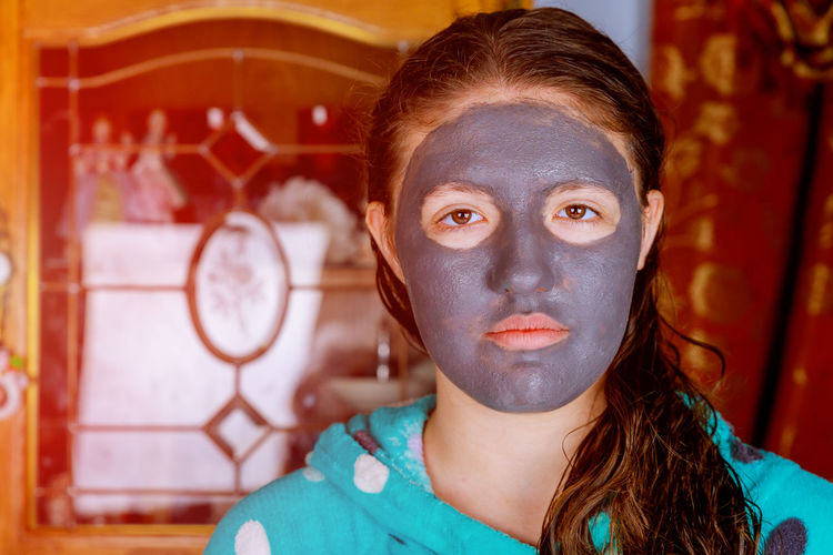Close-up portrait of girl with facial mask at home
