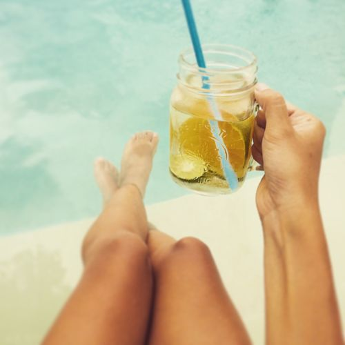Woman Holding Refreshing Drink By Swimming Pool