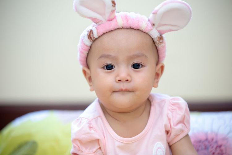 Cute baby girl wearing bunny ears headband at home