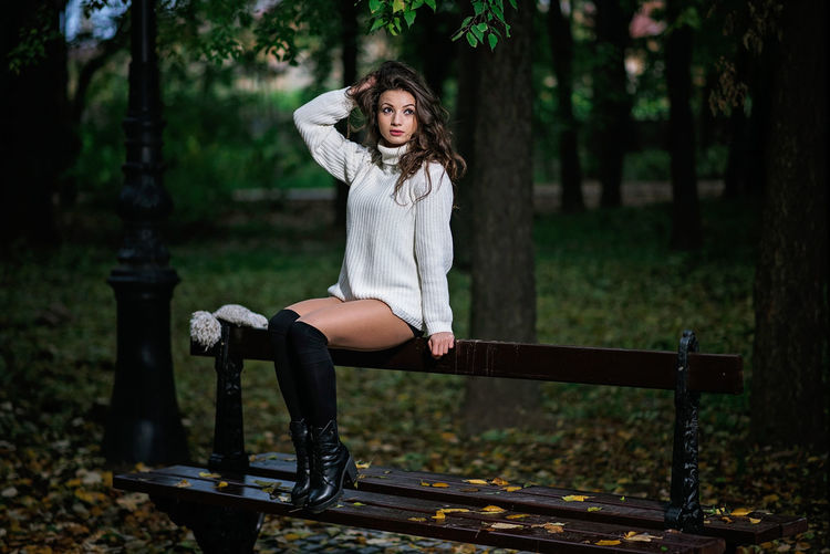 Woman looking away while sitting on bench in park