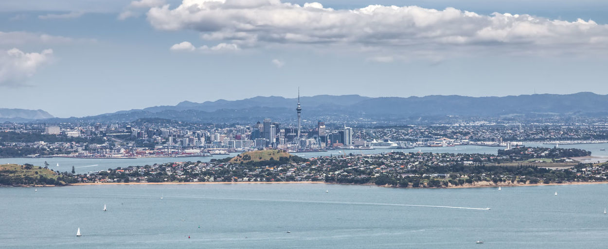 Skyline of Auckland in New Zealand from the top of Rangitoto Island Architecture Auckland Bay Building Business Channel City Cityscape Coastline Distant District Dock Downtown Economy Exterior Finance Futuristic Gulf Harbor Hauraki Island Landscape Lookout Modern Nautical New Zealand Nobody North Island Oceania Office Outdoors Panorama Rangitoto Rippled Sea Sky Skyline Skyscraper Structure Tower Town TOWNSCAPE Travel Destinations Urban Vessel View Volcanic  Wake Water Waterfront Building Exterior Built Structure Cloud - Sky No People Nature Mountain Residential District Day