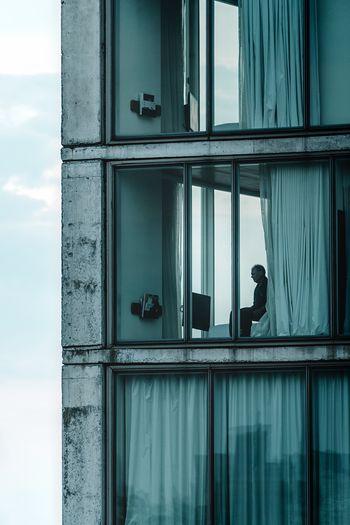 Man on window against sky