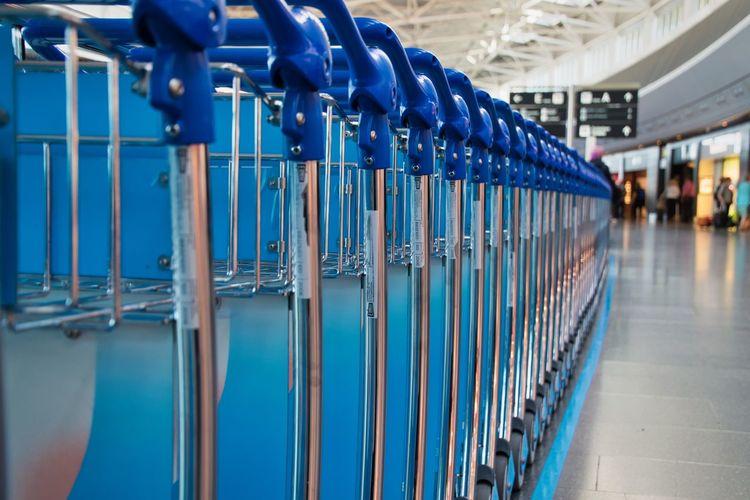 Close-up of blue luggage carts