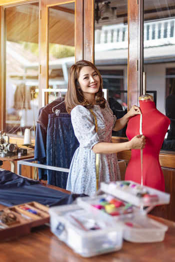 Smiling fashion designer measuring mannequin at fashion studio