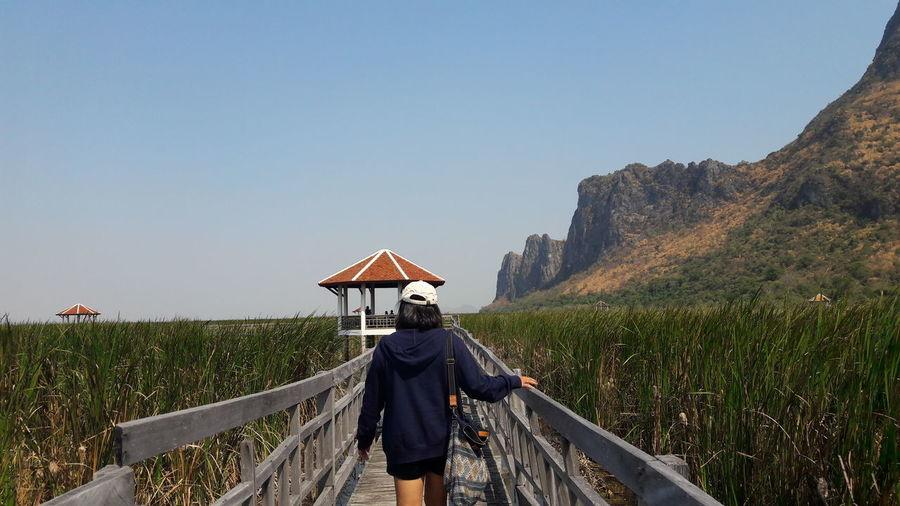 Rear view of woman walking on footbridge against sky