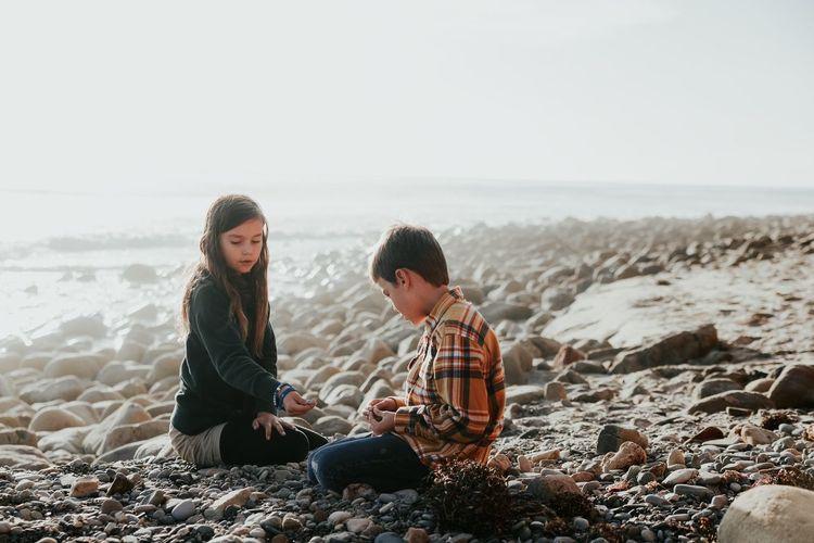 Siblings sitting on rocks at beach against clear sky