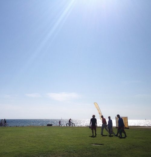 People Walking On Grassy Field By Sea Against Sky