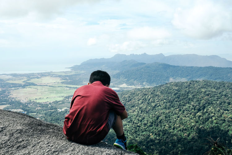 Rear view of boy sitting on cliff against cloudy sky
