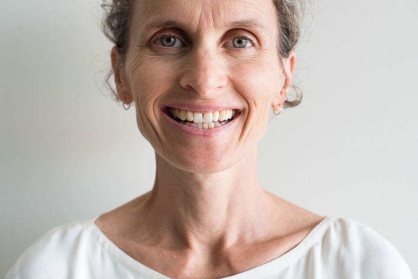 Close up of smiling middle aged woman Adult Close-up Emotion Front View Hairstyle Happiness Headshot Human Face Indoors  Looking At Camera Mature Adult Mature Women One Person Portrait Senior Adult Smiling Studio Shot Teeth Toothy Smile Women