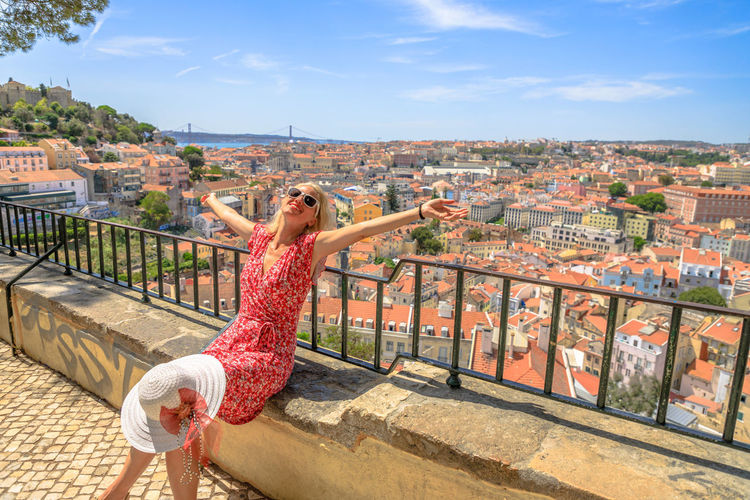 Happy woman with open arms admiring 25 April Bridge, Tagus river and Baixa District from Sao Jorge Castle in Alfama, Lisbon, Portugal. Female tourist enjoys of aerial views. Freedom and travel concept Losbon Woman Girl Tourism Blonde Happy Vacations Portugal Europe Monument City Aerial View Cityscape Skyline Castle In Alfama Panorama Architecture One Person Built Structure Building Exterior Lifestyles Real People Women Sky Young Adult Leisure Activity Day Full Length Young Women Casual Clothing Adult Nature Fashion Railing Outdoors Human Arm Hairstyle Beautiful Woman
