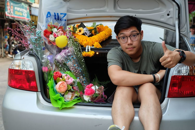 Portrait of young man with bouquet sitting in car trunk