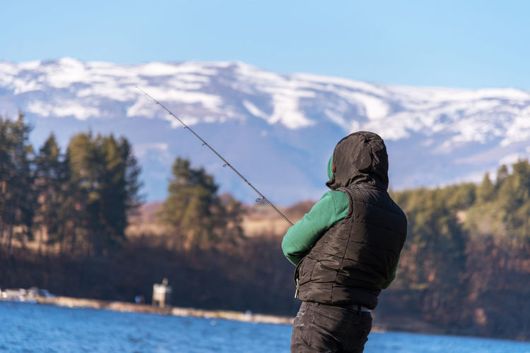 Rear view of a man fishing in lake