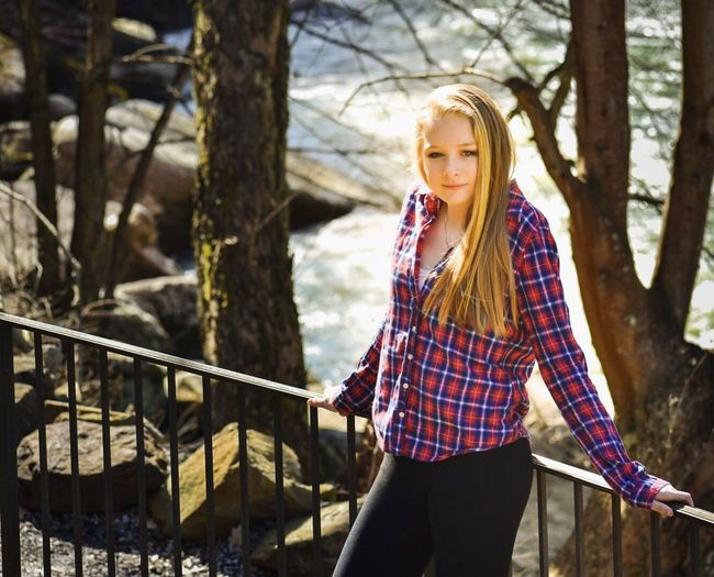 Portrait Of Young Woman Leaning On Railing Against Stream In Forest