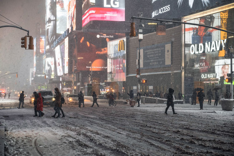 People walking on road in city during winter