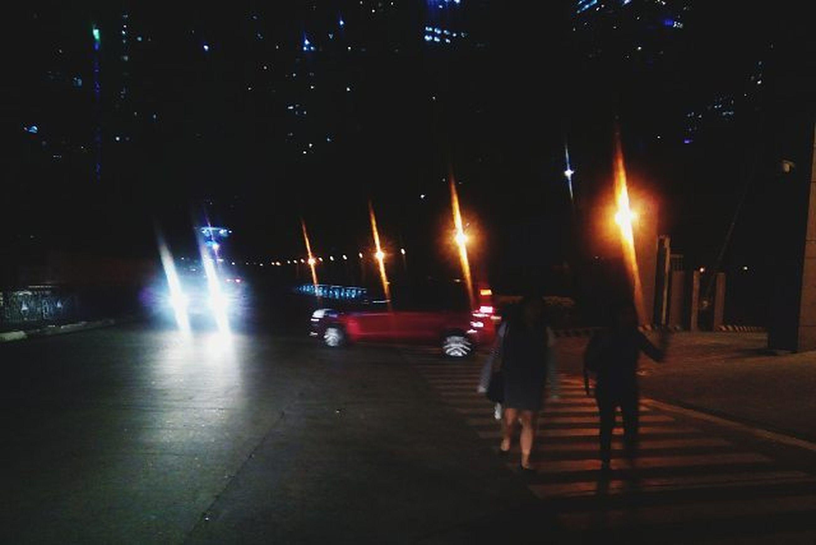 illuminated, night, transportation, men, lifestyles, walking, mode of transport, street light, street, full length, on the move, leisure activity, city life, road, lighting equipment, person, land vehicle, rear view, the way forward