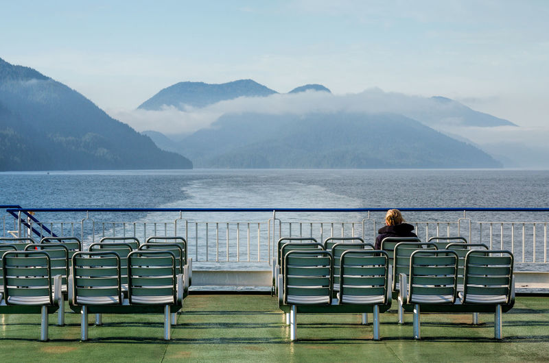 Rear View Of Woman Sitting On Chair At Ship Against Mountains
