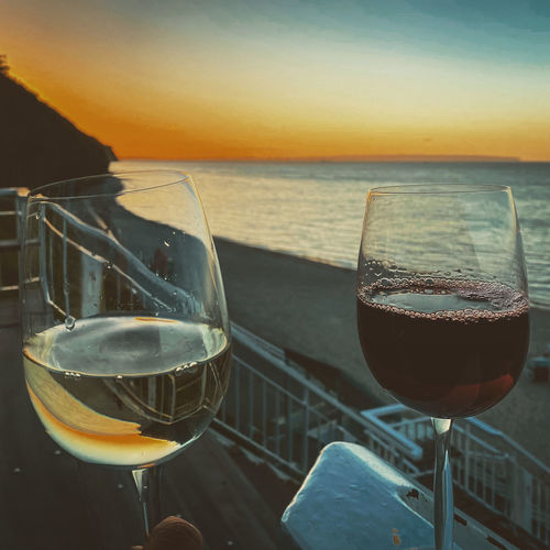 Close-up of wine glass on table against sunset
