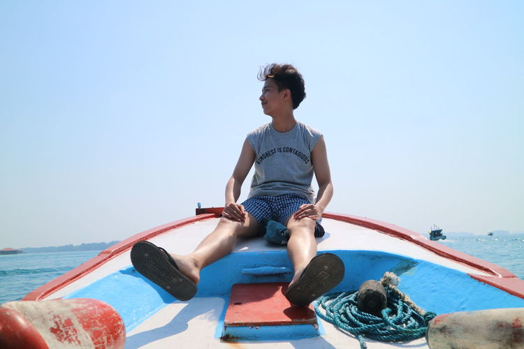 Young man sitting in sea against clear sky