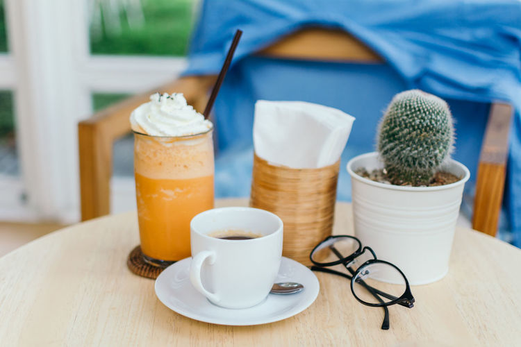 Close-Up Of Drink And Cactus On Table