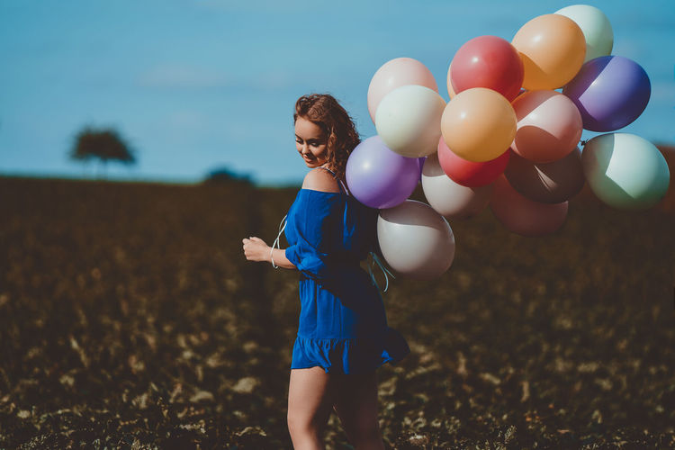 Side view of woman holding colorful balloons while standing on land
