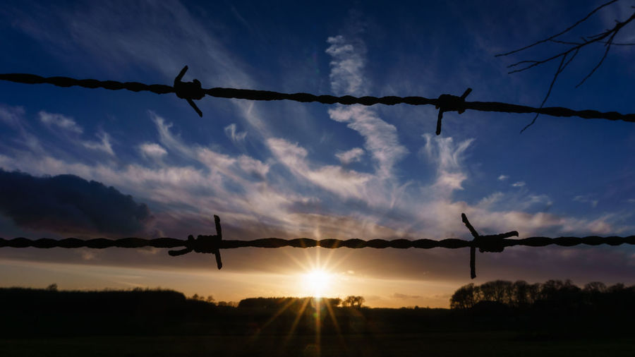 Sky Cloud - Sky Safety Silhouette Sunset Protection Barbed Wire Fence Security Nature Barrier Wire Sun Boundary Metal No People Sunlight Outdoors Lens Flare Orange Color EyeEm Best Shots EyeEm Selects EyeEm Gallery