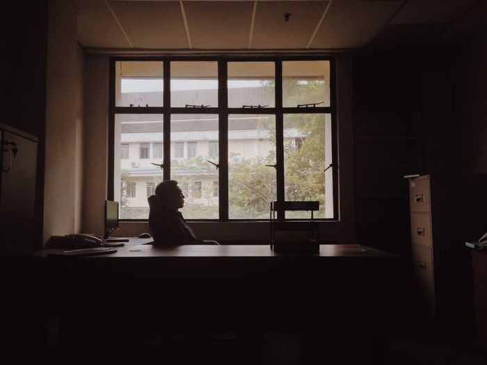 Businessman Sitting On Chair By Window At Office