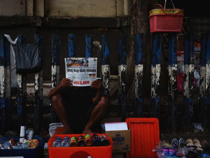 Seller reading a newspaper Newspaper Reading Street Colorful Store Business Finance And Industry Red Occupation Display Market Street Market Market Vendor For Sale Market Stall Raw Retail Display EyeEmNewHere