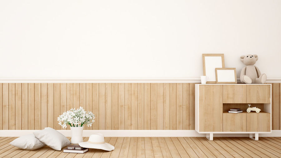 Wooden table and chairs against white wall