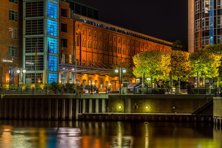 Illuminated building by river at night