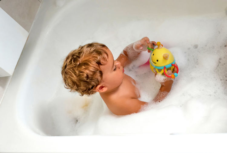 Boy with toys in bathroom at home