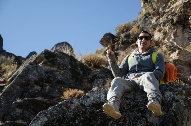 Low angle portrait of man gesturing while sitting on rock against mountains